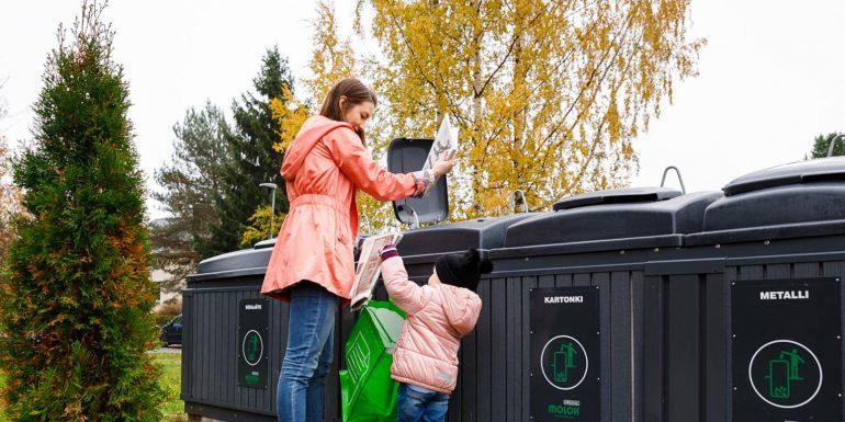 Äiti ja lapsi lajittelevat jätteitä Molok Oy:n valmistamaan syväkeräysastiaan Nokialla.