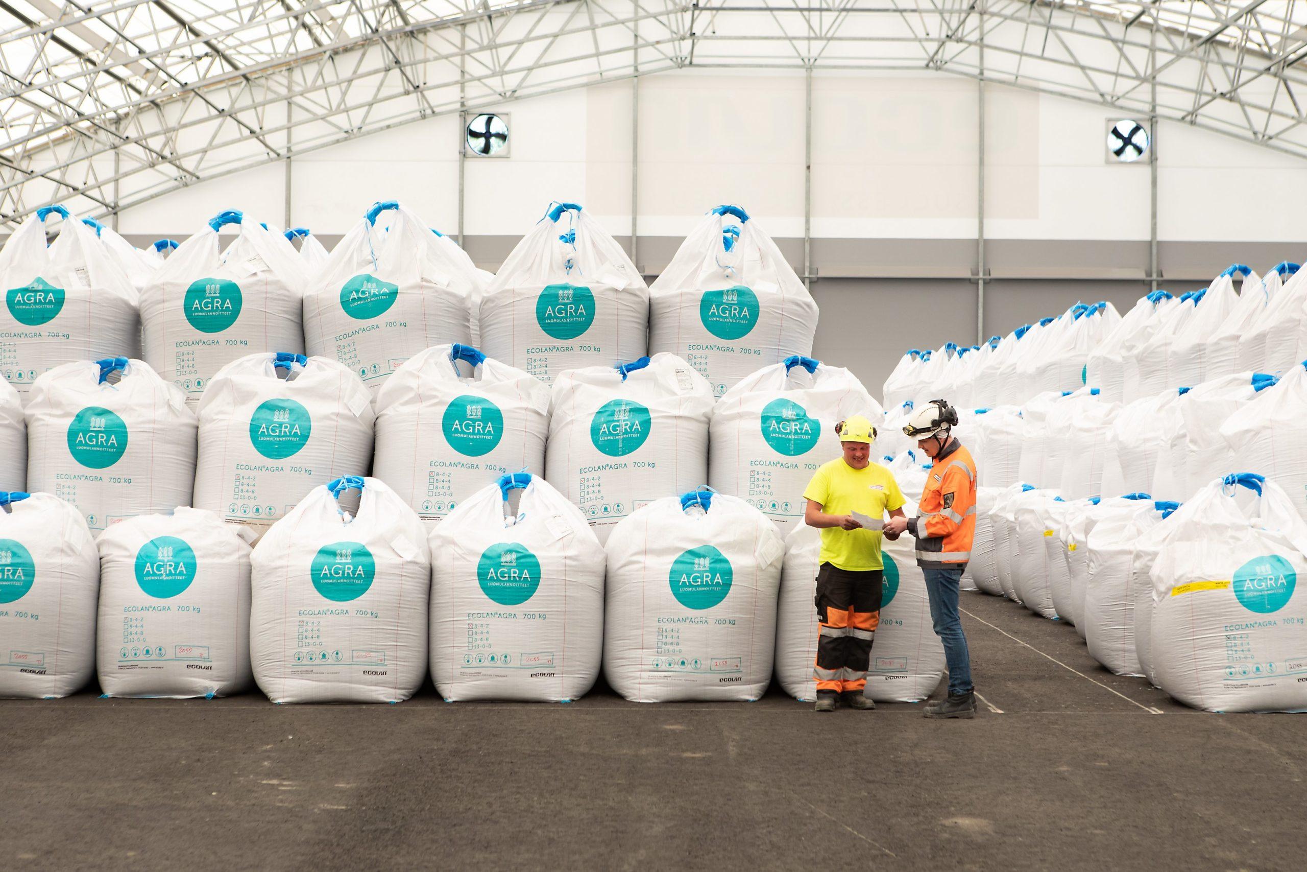 Ecolan Oy:n luomulannoitevarasto, jossa suursäkkejä pinottuna ja säkkien edessä on kaksi yrityksen työntekijää keskustelemassa.