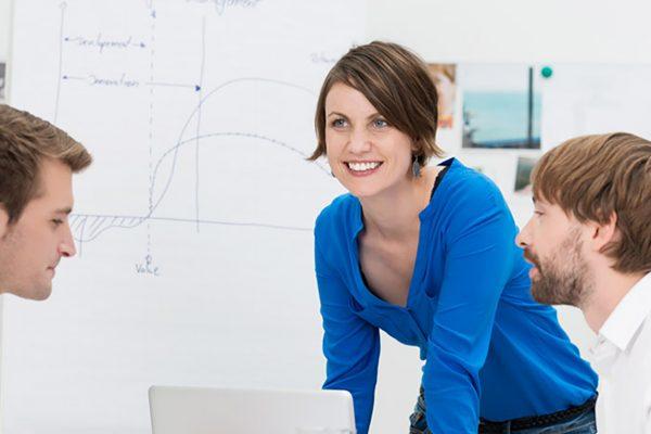Nokian kaupungin yrityspalvelut tukevat aloittavaa yritystä. Hymyilevä nainen pitää koulutusta neuvottelupöydän ympärillä istuville ihmisille toimistossa.