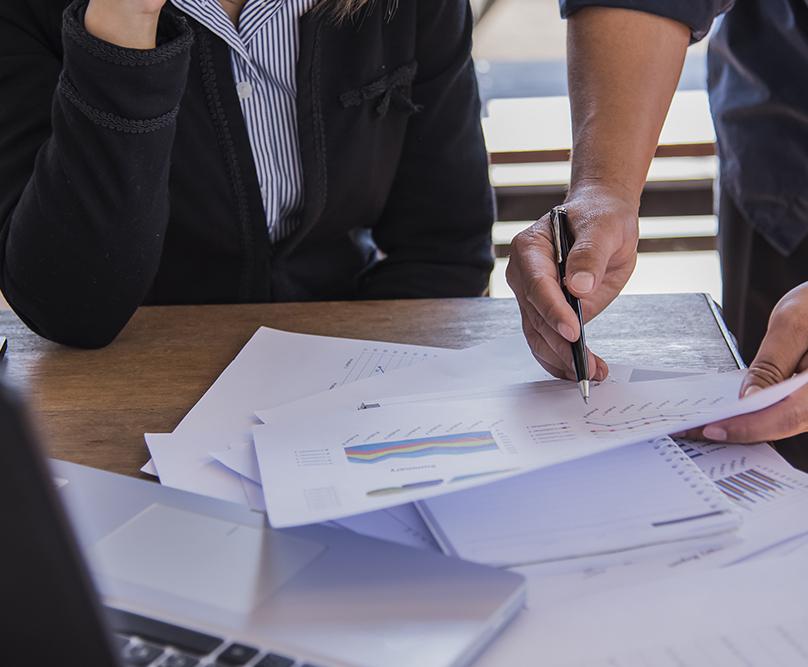 Mies ja nainen käyvät papereita läpi työpöydällä.