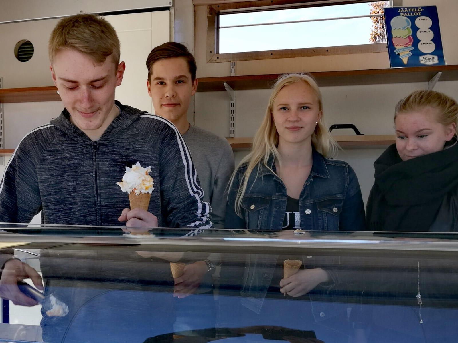 Nokialaiset nuoret yrittäjät jäätelökioskinsa tiskin takana. Yksi nuorista ojenaa jäätelötötteröä.