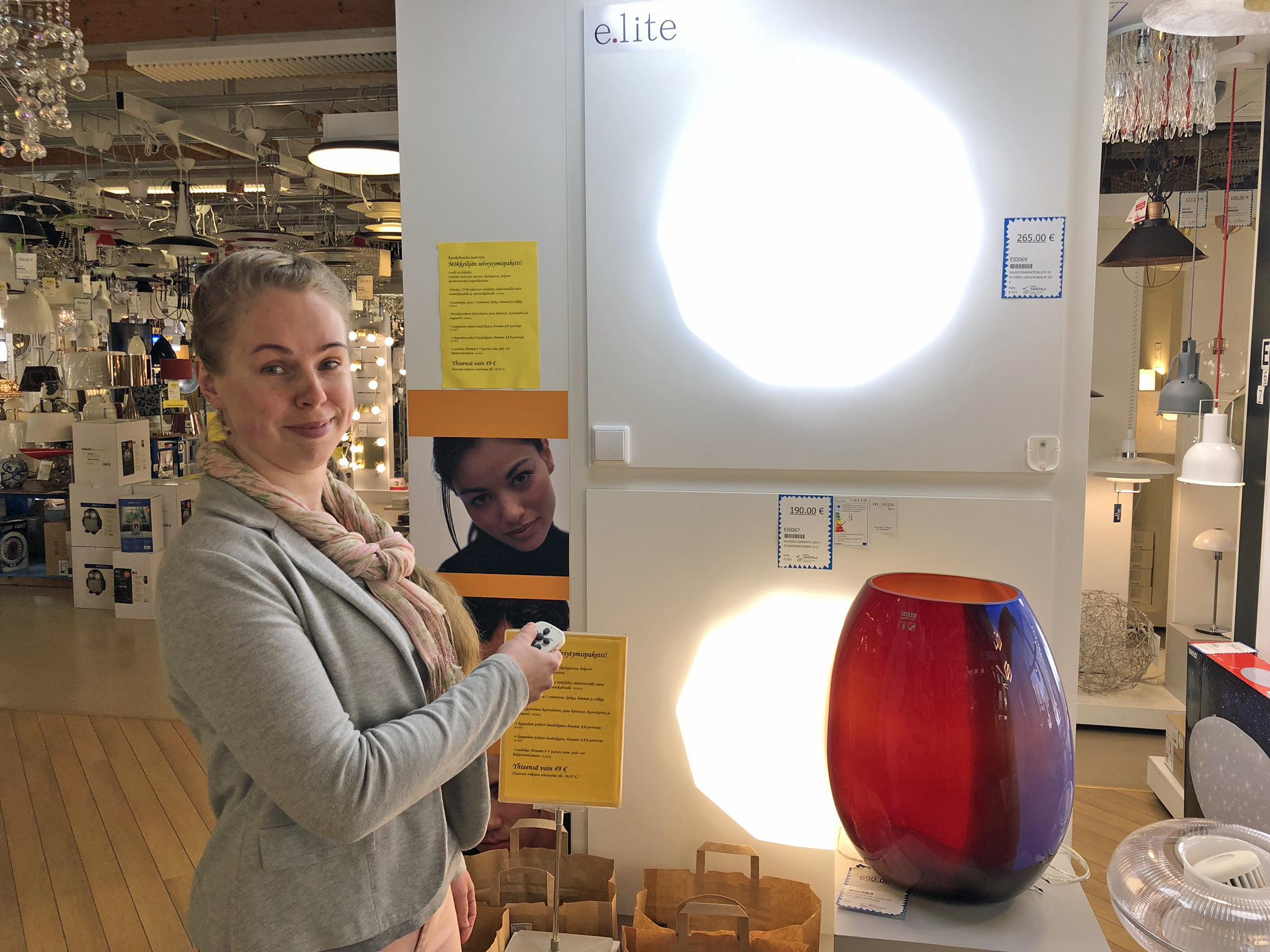Suvi Sorva esittelee Nokian Sähkötalon erikoisvalaisimia myymälässä.