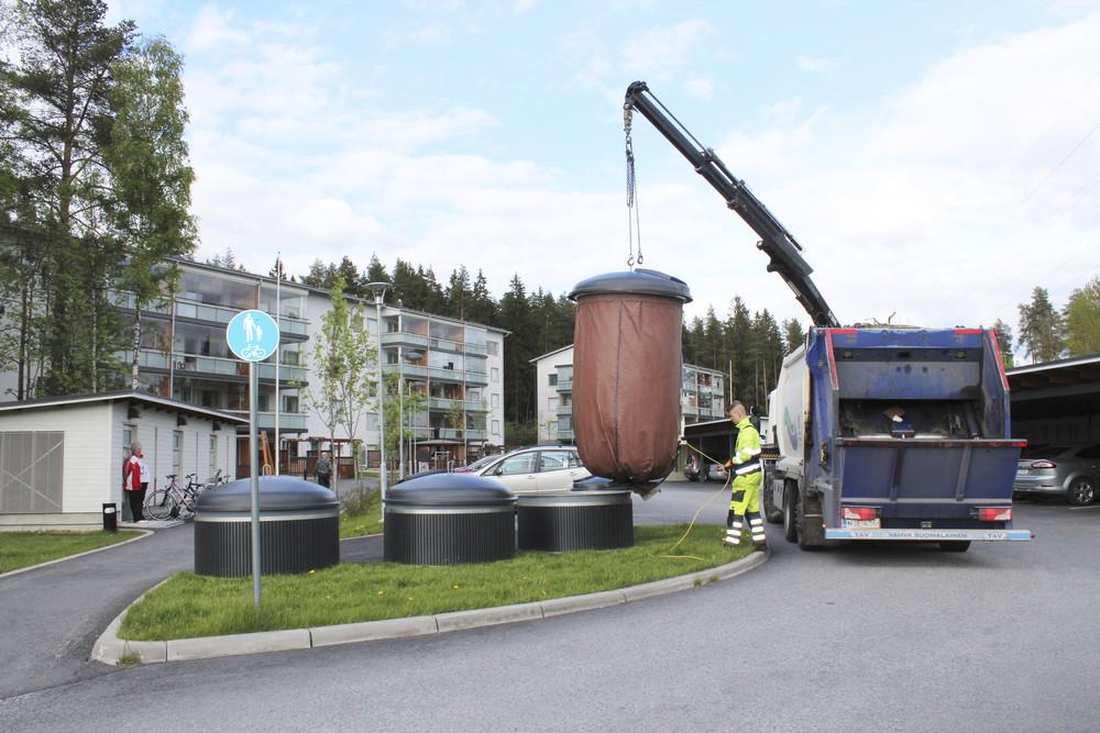 Jäteauto tyhjentää Molok-syväkeräysastiaa nosturilla kerrostalon jätepisteellä.