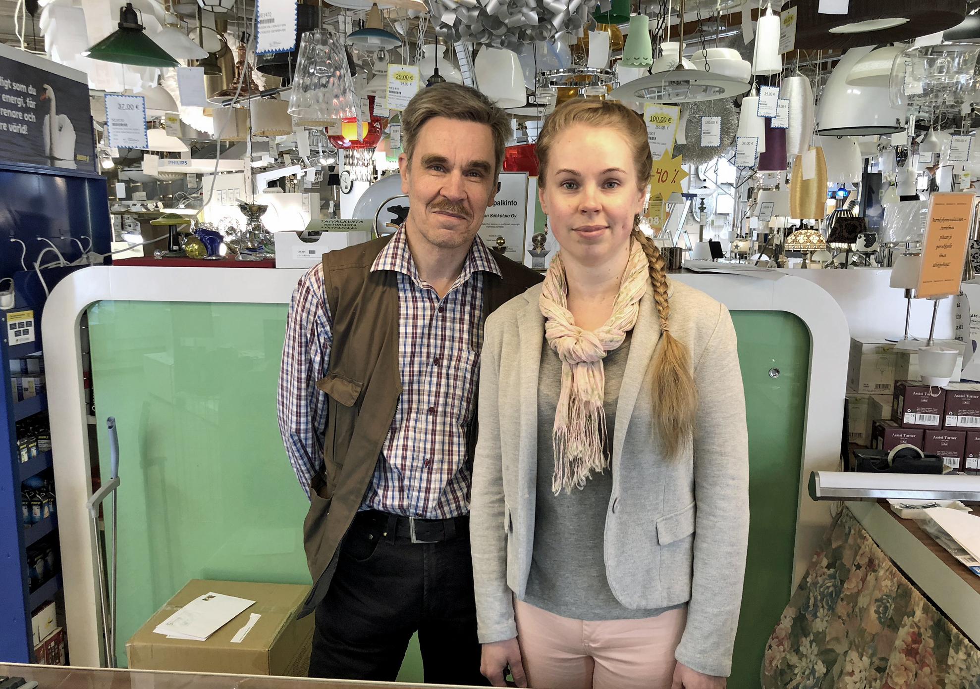 Nokian Sähkötalon yrittäjä Olli Sorva ja tytär Suvi Sorva, joka myös työskentelee yrityksessä, seisovat kassalla takanaan satoja lamppuja, jotka roikkuvat katosta.