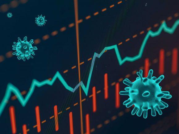 Mikroskoopilla suurennettuja koronaviruksia tietokoneen ruudulla. Virusten takana näkyvät laskevat osakekurssit.