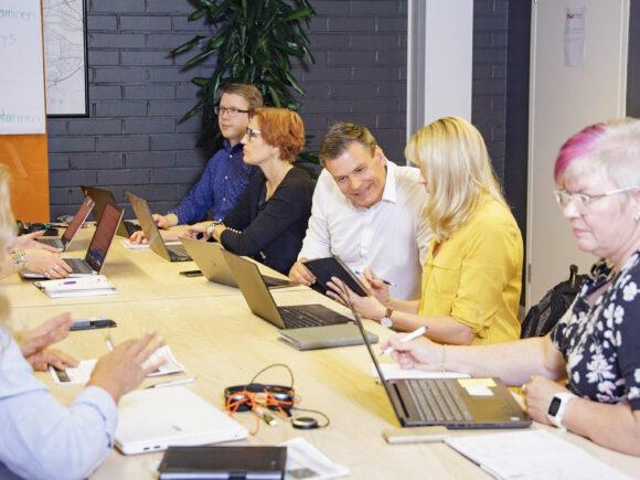 Kokouspöydän äärellä on aikuisia tekemässä ryhmätyötä.