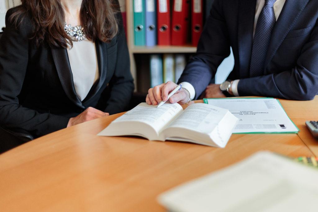 Pöydän ääressä istuu kaksi henkilöä, jotka katsovat pöydällä olevaa kirjaa.