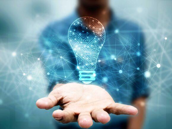 Miehen ojennetun käden päällä on kuvitteellinen sähkölamppu kuvaamassa uuden innovaation syntymistä.
