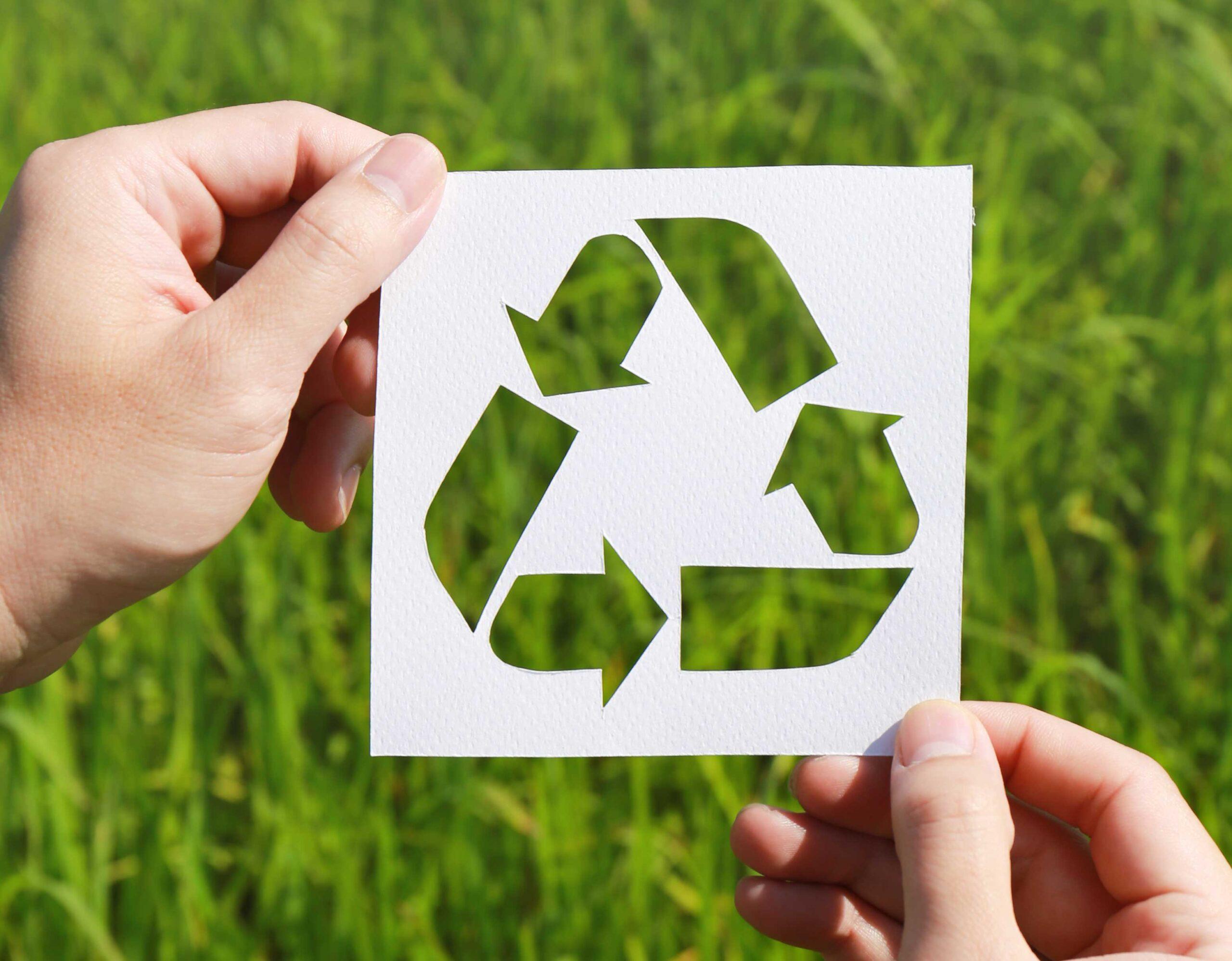 Kädet pitelevät valkoiseen paperiin leikattua kierrätysmerkkiä vihreän nurmikon päällä.