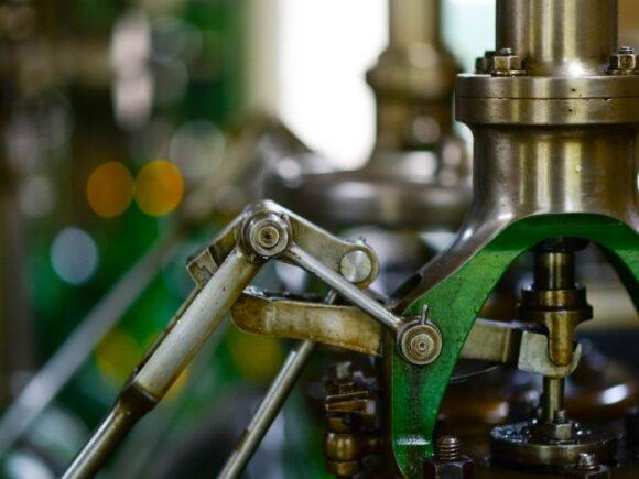 Metallisen koneen osat ovat kullan ja vihreän värisiä.