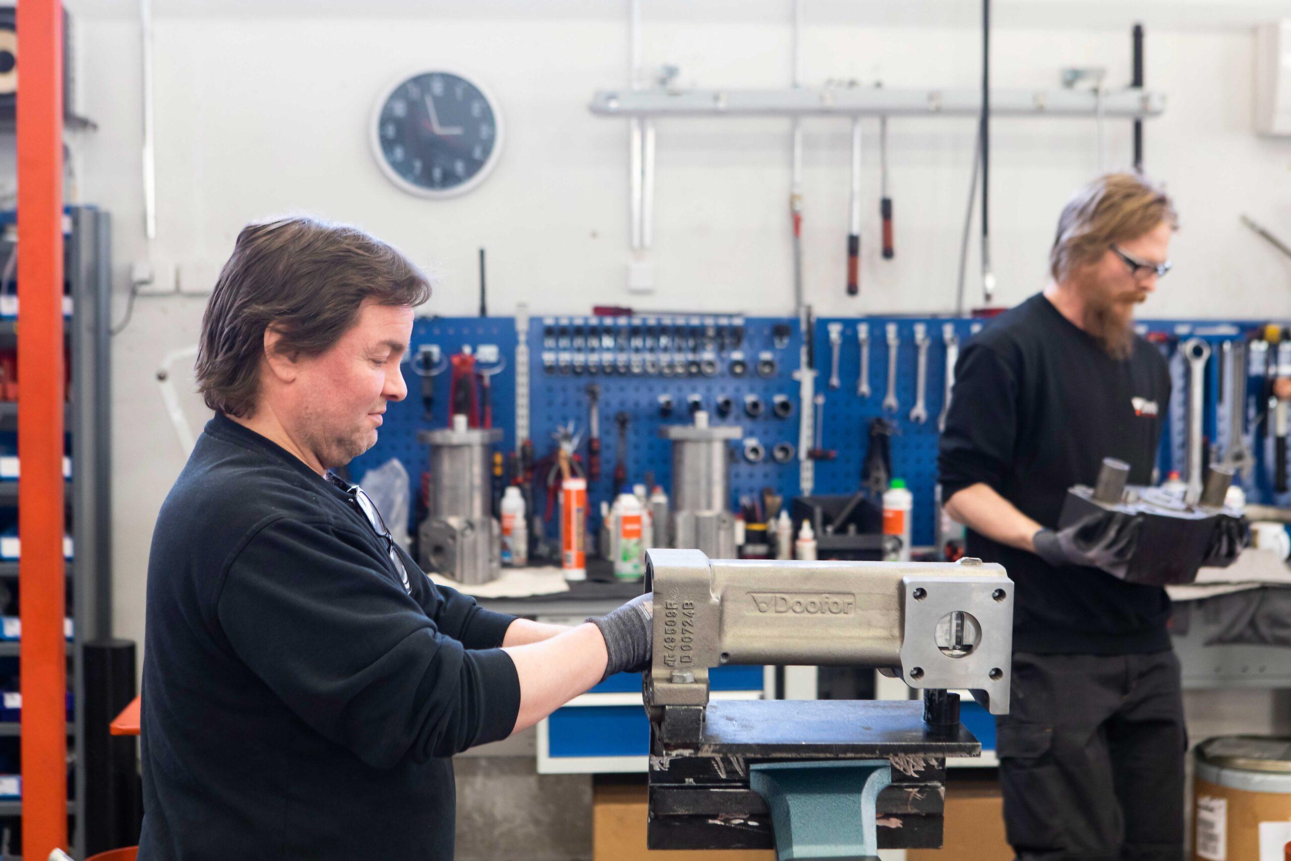 Kaksi Dooforin asentajaa kokoamassa poria yrityksen tuotantotiloissa.