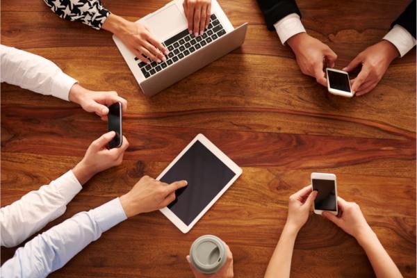 Pöydän ympärillä on ihmisiä, joilla on käsissään puhelimia, tabletteja ja läppäri.