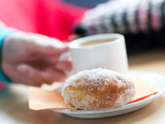 Käsi pitelee kiinni kahvikupista ja sen edessä on lautasella sokerinen munkki.