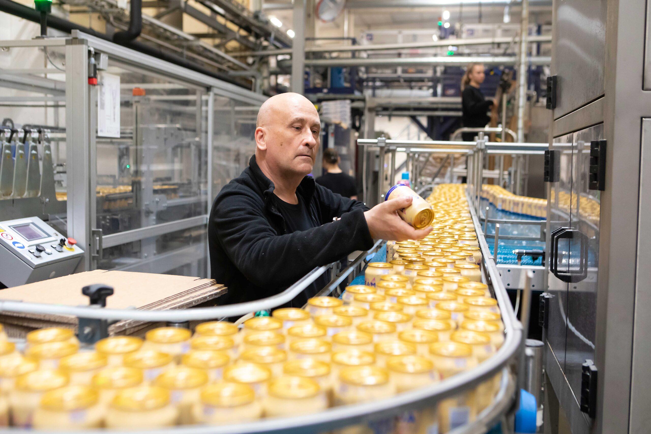 Mies tarkastelee virvoitusjuomatölkkiä Nokian Panimon tuotantolinjalla.