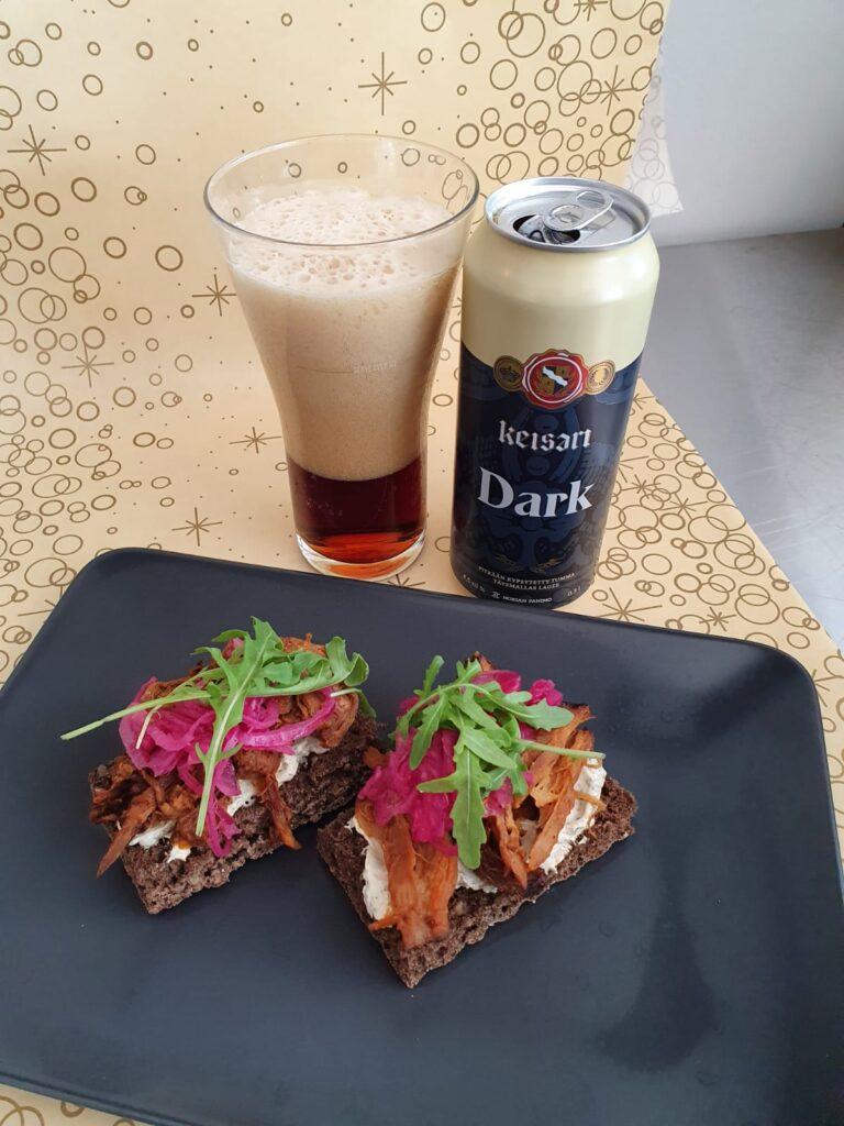 Bistro Minean maisteluannoksessa on leipäsiä ja niiden vieressä Nokian Panimon tummaa olutta tuopissa ja tölkissä.