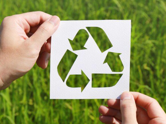 Henkilö pitää käsissään valkoista paperia, johon on leikattu kierrätysmerkki. Takana näkyy vihreää nurmikkoa.