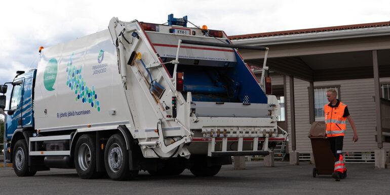 Pirkanmaan Jätehuollon työntekijä kuljettaa ruskeaa biojäteastiaa kohti jätteenkuljetusautoa.