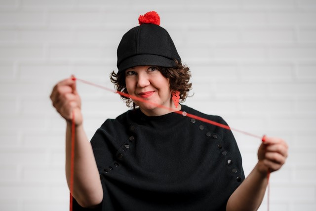Mustiin pukeutunut nainen pitää käsissään punaista lankaa.