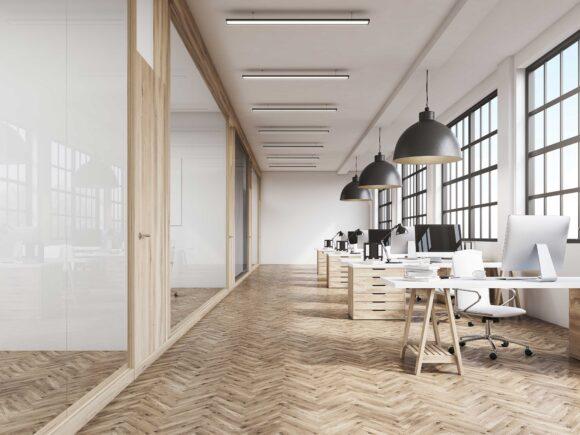 Tyhjä toimistotila, jossa on valkoiset seinät, puunvärinen lattia ja vaaleita toimistokalusteita.
